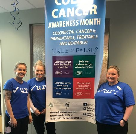 Office staff with a colon cancer awareness banner.