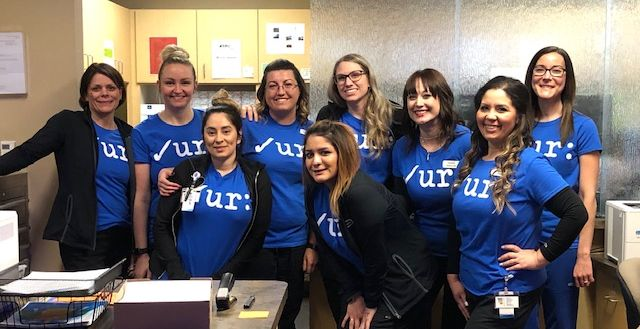 """Office photo with staff in their """"Check Your Colon"""" Tshirts."""